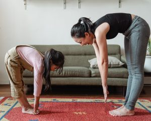 woman and child stretch down to touch their toes